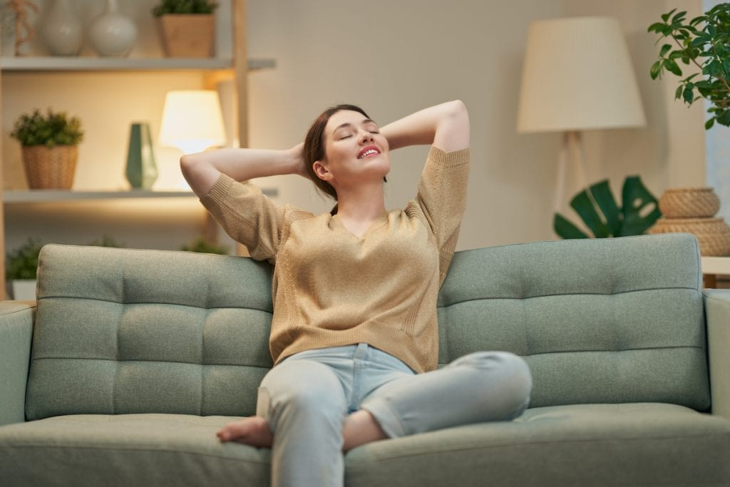 a young woman resting at home on her sofa